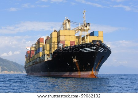 Large container ship in mediterranean coast - stock photo