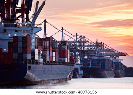 large container ships freighters in a busy port harbor during sunset - stock photo