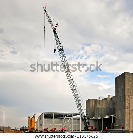 Large crane at a construction site. A new facility build in a suburban community creating new jobs. - stock photo