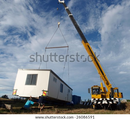 Large Crane lifting a temporary housing unit into place - stock photo