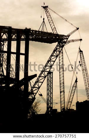 Large Crane Silhouette lifting a large Steel Piece - stock photo