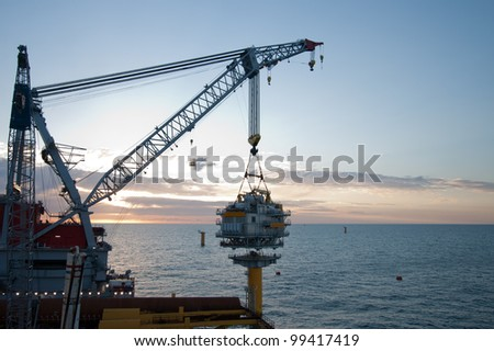 Large crane vessel installing a transformer platform in a windfarm under construction of the UK coast - stock photo