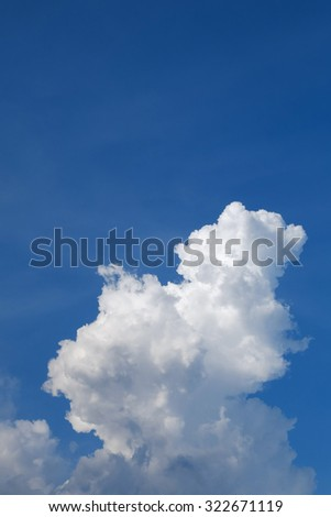 large cumulus cloud on clear blue sky background - stock photo