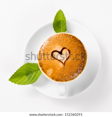 large cup of coffee with heart pattern on the foam and green leaf of mint - stock photo