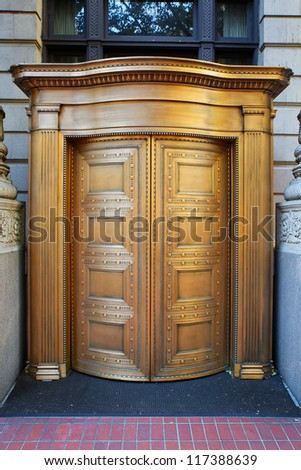 Large curved brass closed doors on a bank entrance - stock photo