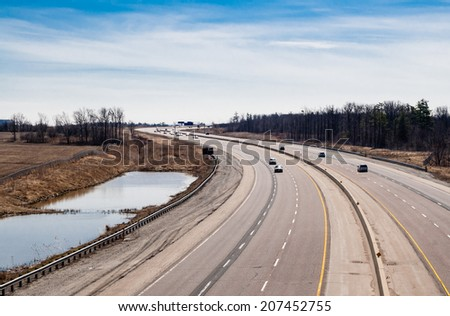 Large curving highway in rural area on cloudy sky. - stock photo