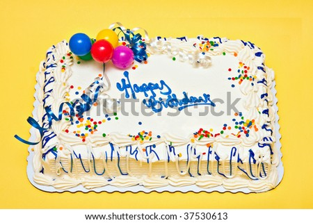 Large decorated Birthday cake with white icing, sprinkles, ribbons, balloons. - stock photo