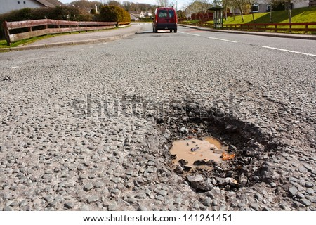 Large deep pothole an example of poor road maintenance due to reducing local council repair budgets - stock photo
