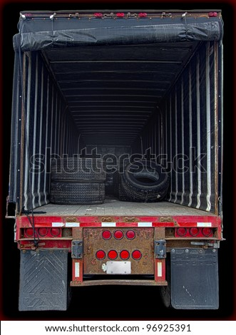 Large delivery truck interior showing nearly empty cargo space viewed from back of vehicle. Low-key lighting, vertical layout, isolated on black background, and copy space. - stock photo