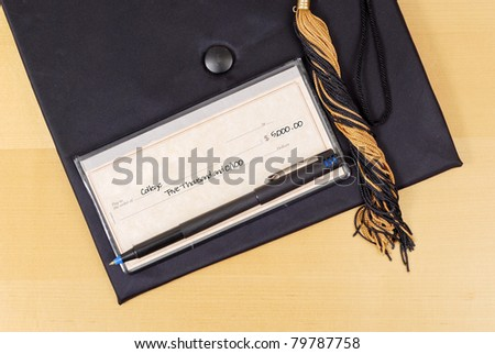 Large Denomination Bank Check on Graduation Cap - stock photo