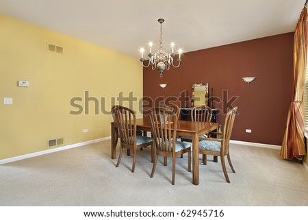 Large dining room with yellow and copper colored walls - stock photo