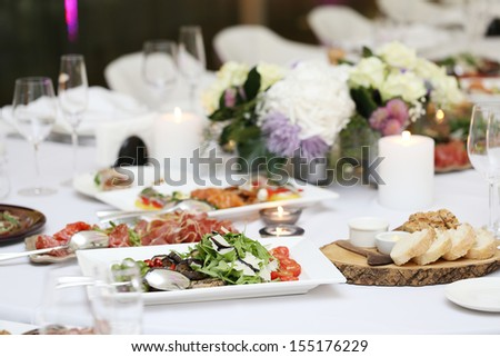 Large dining table with flowers and lots of different kinds of food at a celebration - stock photo