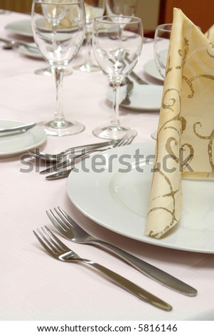 large dinner table set up for a lot of people - stock photo