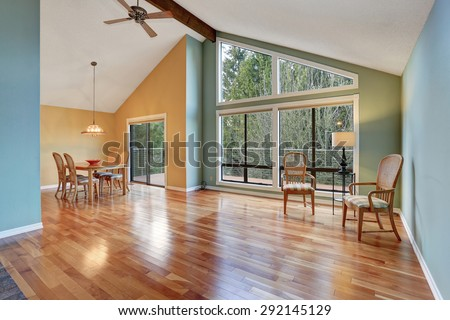 Large dinning area with hardwood floor and big windows. - stock photo
