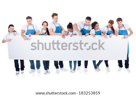 Large diverse group of cleaners or janitors wearing aprons holding a blank white banner with copy space for your text  isolated on white