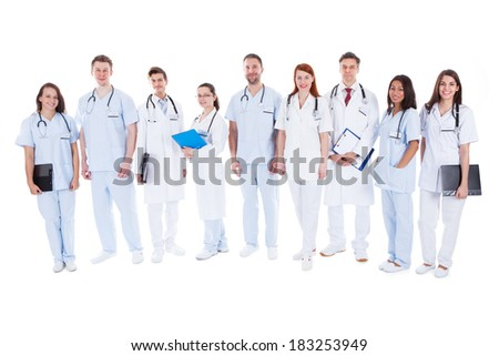 Large diverse group of doctors and nurses in uniform standing in a line holding files of patient records and wearing stethoscopes  isolated on white