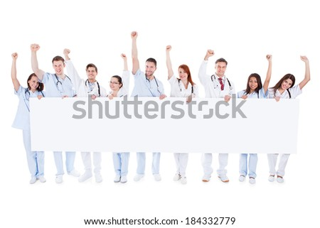 Large diverse group of healthcare personnel standing in a line holding a blank white banner with copyspace and cheering raising their fists in the air isolated on white - stock photo