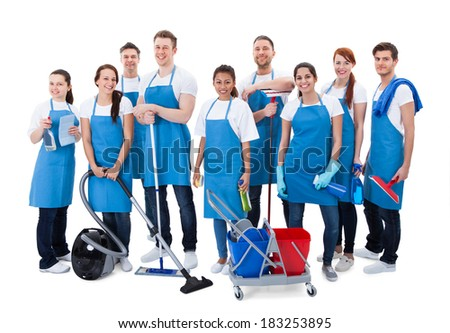 Large diverse group of janitors wearing blue aprons standing grouped together with their equipment smiling at the camera  isolated on white - stock photo