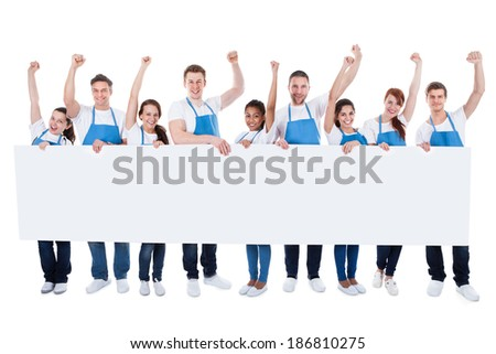 Large diverse multiethnic group of cleaners wearing aprons cheering as they hold a long blank white banner with copyspace for your text or advertisement  isolated on white - stock photo