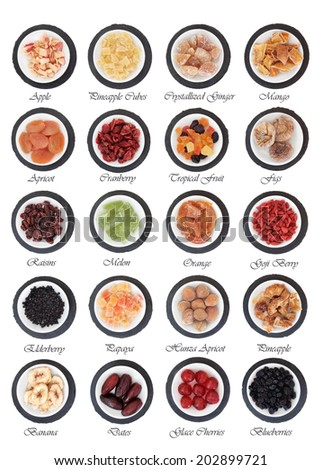 Large dried fruit selection in white bowls on slate rounds over white background with titles - stock photo