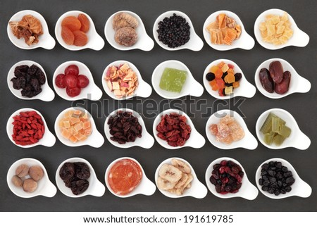 Large dried fruit selection in white bowls over slate background. - stock photo