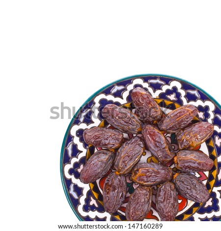 large dry dates are large painted on a plate isolated on white background - stock photo