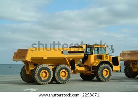 Large dumper trucks working in industrial site - stock photo