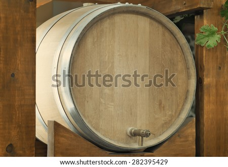 Large durable , made of natural oak, barrel for wine with a metal crane, is located on a convenient wooden stand.