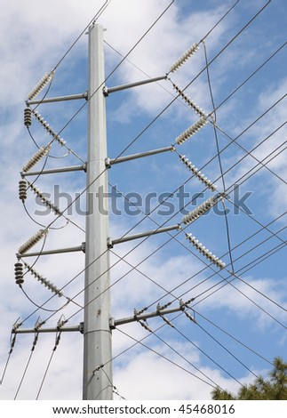 large electrical utility pole with many power lines against sky background