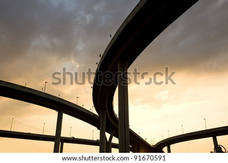 Large elevated traffic highway at sunset - stock photo