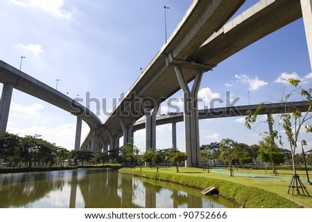 Large elevated traffic highway with pond - stock photo