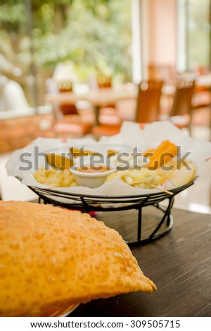 Large empanada on wooden table next to basket of typical latin foods, refreshing restaurant setting. - stock photo