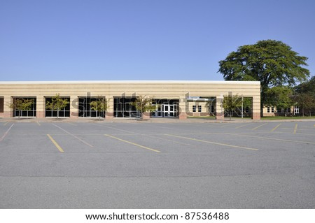 Large empty macadam parking area by an modern school building - stock photo