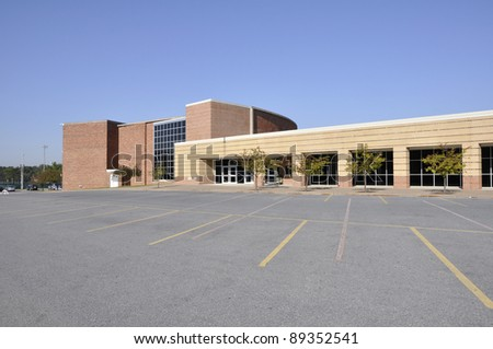Large empty macadam parking lot by a modern school building - stock photo