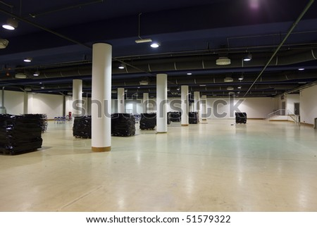 Large, empty warehouse. Ventilation and lighting equipment is mounted on ceiling. - stock photo