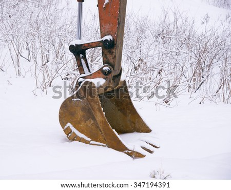 large excavator bucket on ground covered with snow  - stock photo