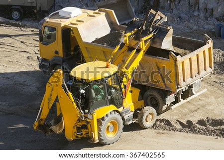 large excavator works carrying debris into a truck in highway construction site - stock photo