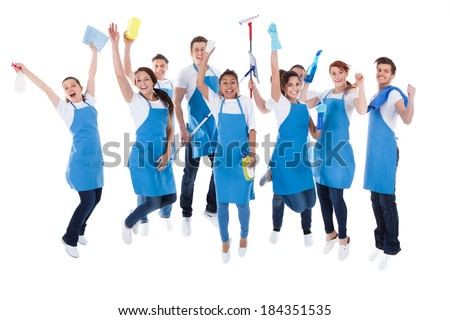 Large excited group of diverse multiethnic janitors jumping and cheering as they celebrate together as a team isolated on white - stock photo