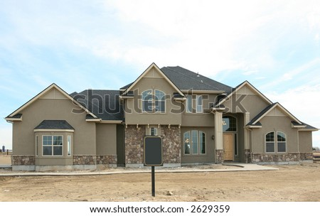 Large expensive modern house with blank sign out front - stock photo
