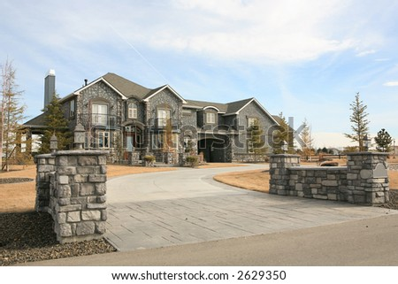 Large expensive modern house with gray stone front - stock photo