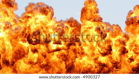 Large explosion, debris can be seen flying in sky - stock photo