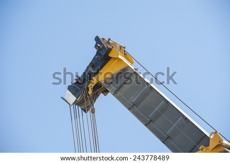 Large extended industrial crane jib boom arm against a blue sky background - stock photo