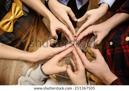 Large family folded her hands in the shape of hearts. - stock photo