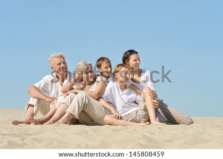 large family resting on the sand in the summer together - stock photo