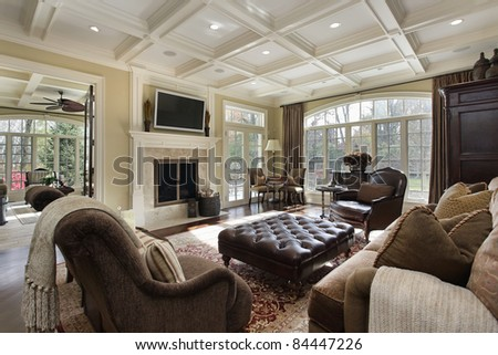 Large family room with fireplace and wall of windows - stock photo