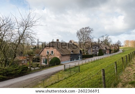 Large farm houses with a thatched roof along a dike in the Netherlands on a cloudy day at the end of the winter period. - stock photo