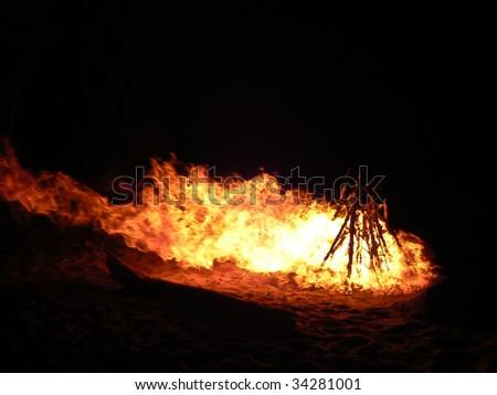 Large fire on sandy beach - stock photo
