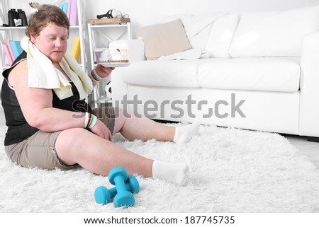 Large fitness man eating unhealthy food and trying to take exercise  at home - stock photo