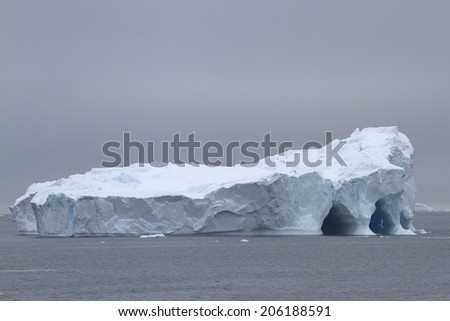 large flat iceberg with several caves - stock photo