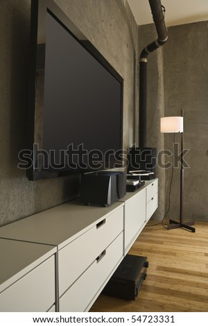 Large flat panel television and entertainment center in a modern loft. Vertical shot. - stock photo